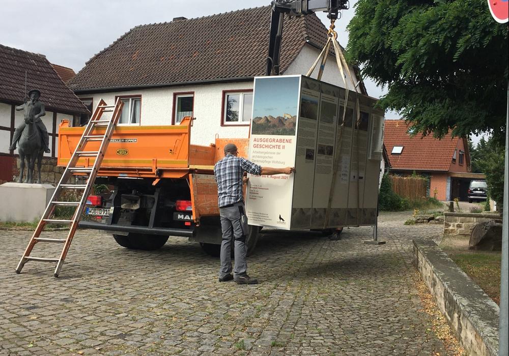 Ein Krahn hebt die mobile Ausstellungsbox an ihren neuen Standort am Hehlinger Roland.
