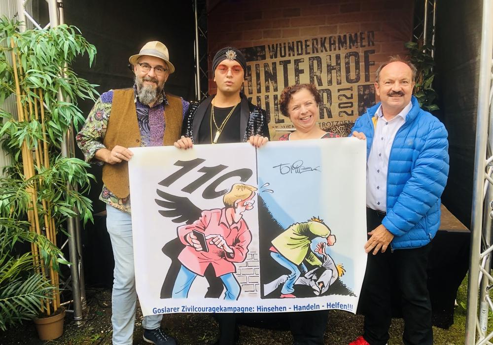 """Marco Assmann, Julian FM Stoeckel, Franziska Traub und Günter Koschig fordern mit dem GZK-Cartoon zum """"Hinsehen, Handeln und Helfen und 110 wählen auf."""