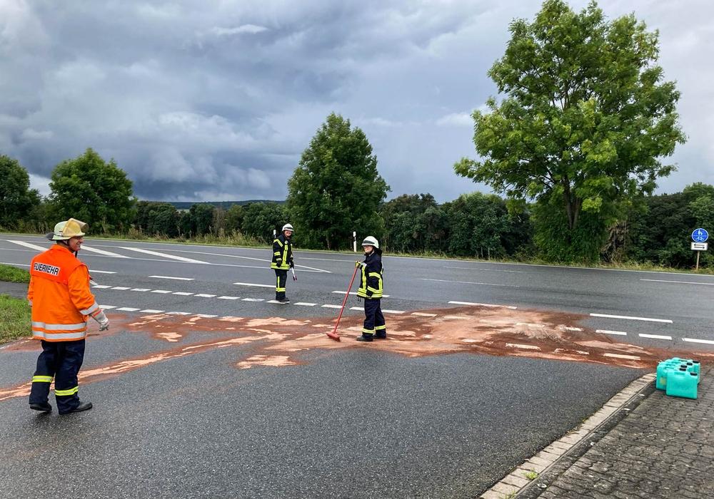 Feuerwehrleute beim beseitigen der Dieselspur.