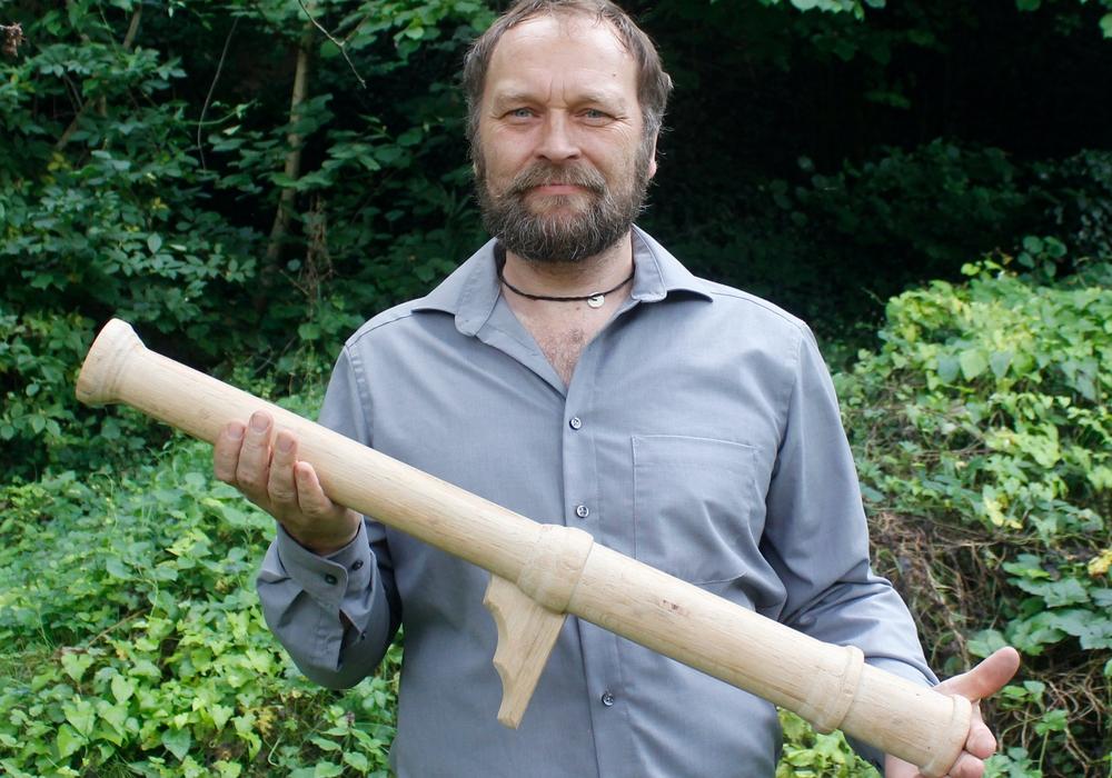 Dr. Bastian Asmus mit dem von ihm gefertigten Holzmodell des Laufs der Hakenbüchse.