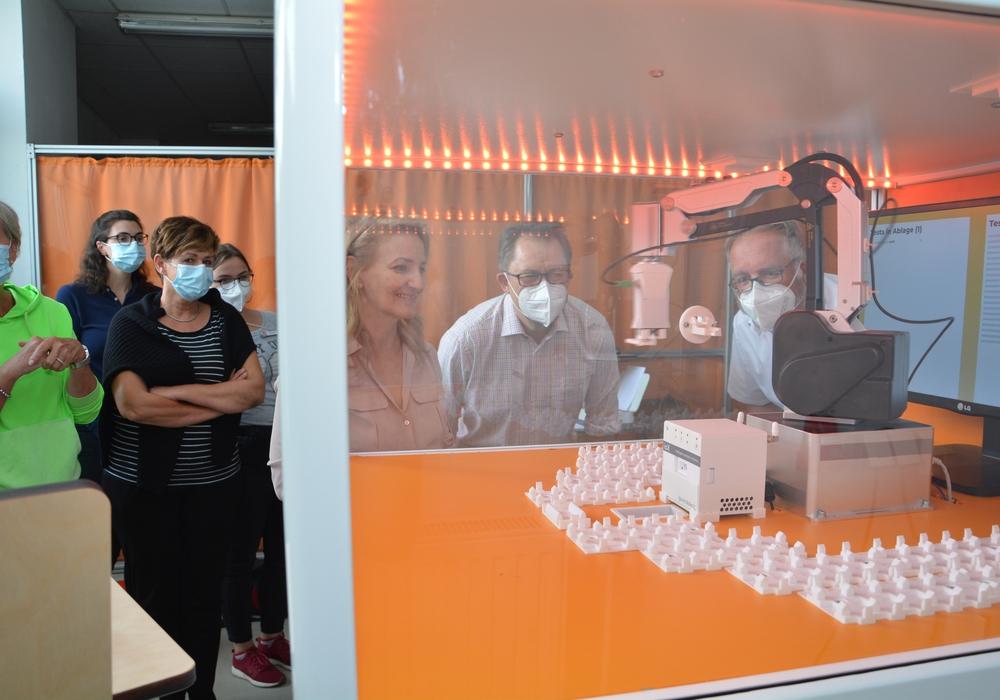 Der Roboter hat den Teststreifen aus dem Eingabeschlitz genommen und schiebt ihn gleich in das weiße Testgerät hinein. Dabei wird er beobachtet von den DRK-Mitarbeitern des Testzentrums (links) sowie (von rechts) Thomas Stoch, Jens Uphoff und Karima Berrahou, die den Ablauf erklärte.