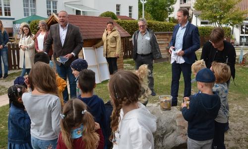 """ur Eröffnung der """"Spielkiste"""" (im Hintergrund) hat Helmstedts Bürgermeister Wittich Schobert Gummibärchen für die Kinder mitgebracht."""