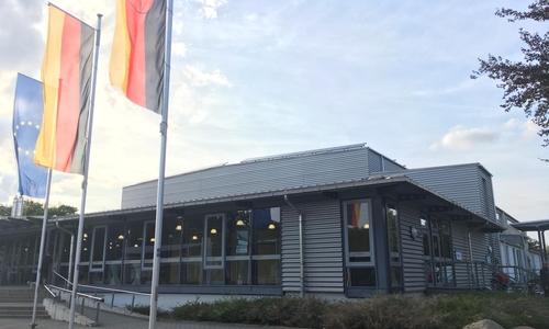 Die Flaggen der EU, Deutschlands und Niedersachsens sind vor der Lindenhalle gehisst.