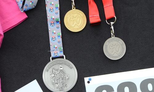 Die Finishermedaille, ganz links, gibt es für jeden Sportler der das Ziel erreicht.